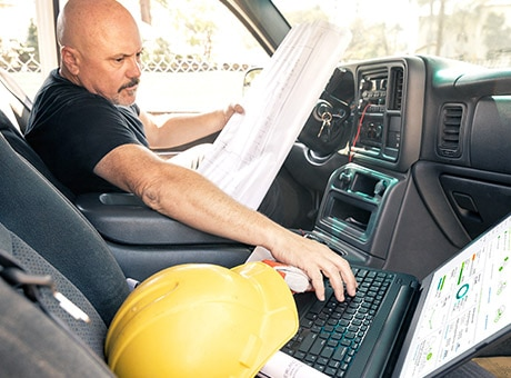 Wind farm foreman reviews plans on site in his truck