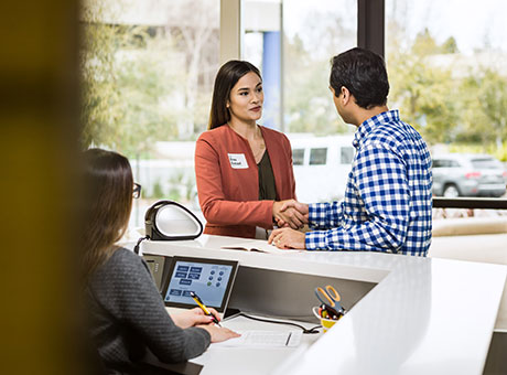 Small business owner rewards employee for good attendance in office lobby