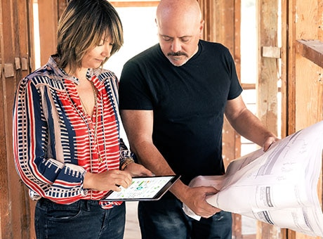 Remodeling business owner and client review an estimate and floorplans