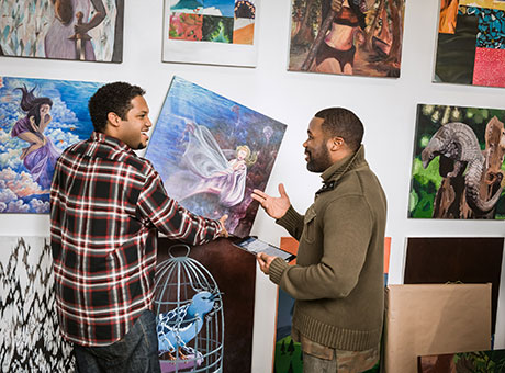 Art gallery employees engage with each other while arranging art work