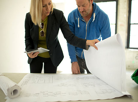 Small business owner reviews blueprints with independent contractor