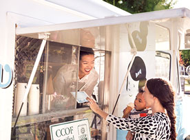 Mobile ice cream truck entrepreneur engages with a customer