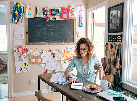 Home-based small business owner reviews e-commerce expenses on tablet