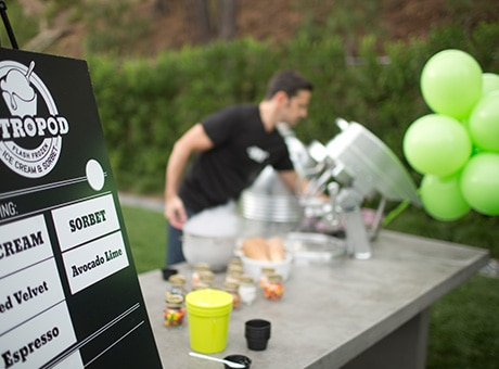 Employee sets up an outdoor table with balloons for a business's grand opening