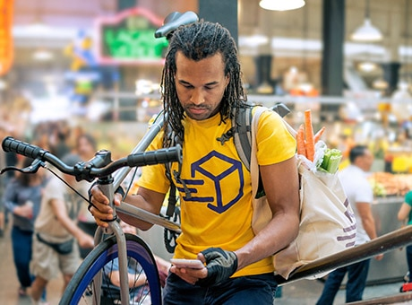 Man with bicycle uses a small business mobile app