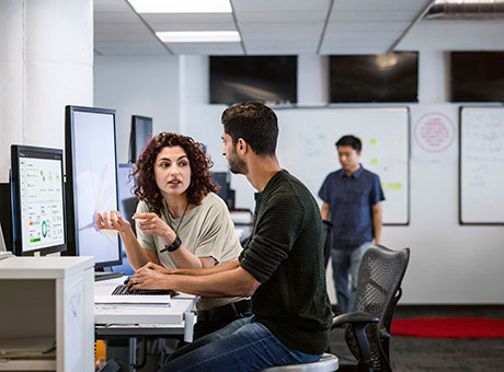 Woman training a man to use office software