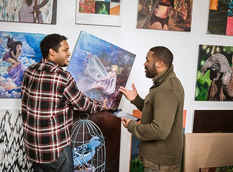 An artist hangs a painting in an alternative gallery space