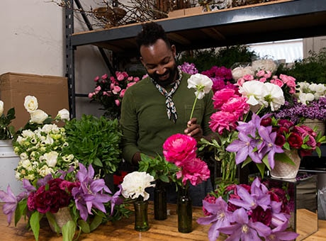 A freelance florist prepares bouquets for customers