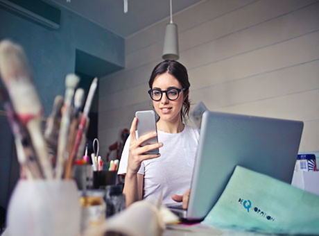 Canadian small business owner reviews tariffs on her smartphone