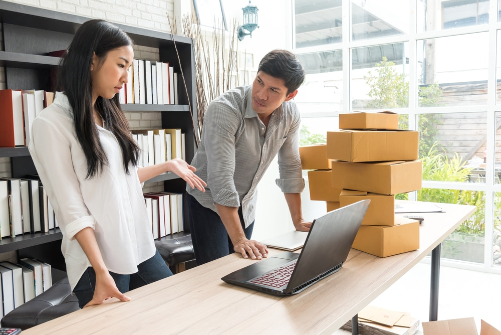 Business owners standing over a desk while looking at a cloud OMS. There is a stack of boxes next to them.