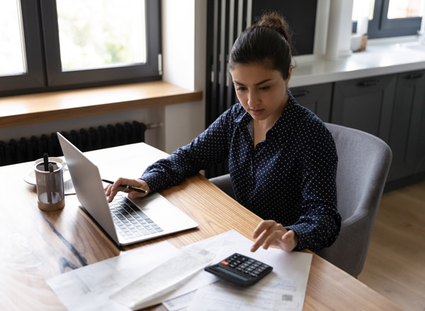 Woman sitting at her desk using a calculator to double-check her calculations while referencing her laptop.