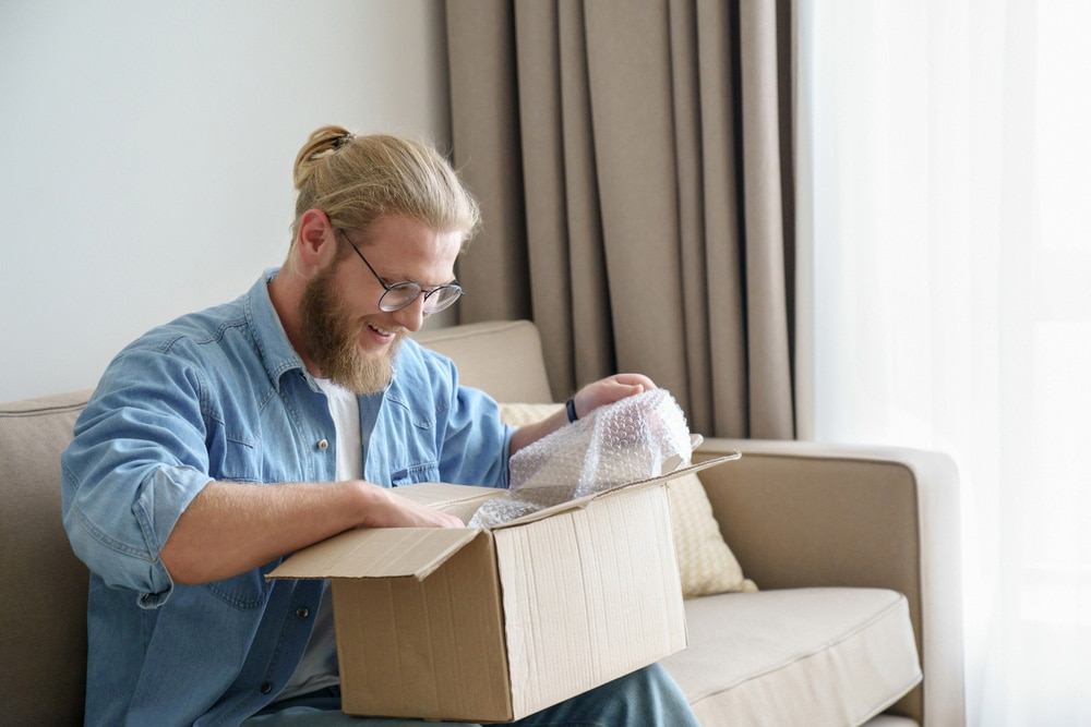 Man smiling while unboxing a package.