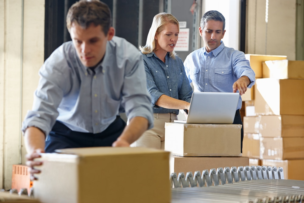 Three employees handling distribution while two discuss something on their laptop.