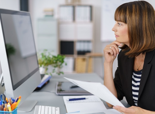 Woman sitting at her desk, holding a piece of paper and looking at her desktop monitor thoughtfully.