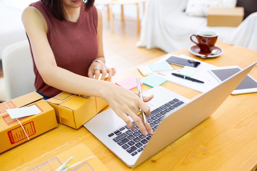 Woman sitting at a desk in front of an open laptop while addressing shipping boxes
