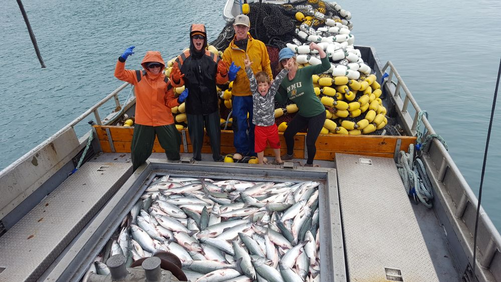 The crew, including Megan's sons, posing with a completely full hold of fish