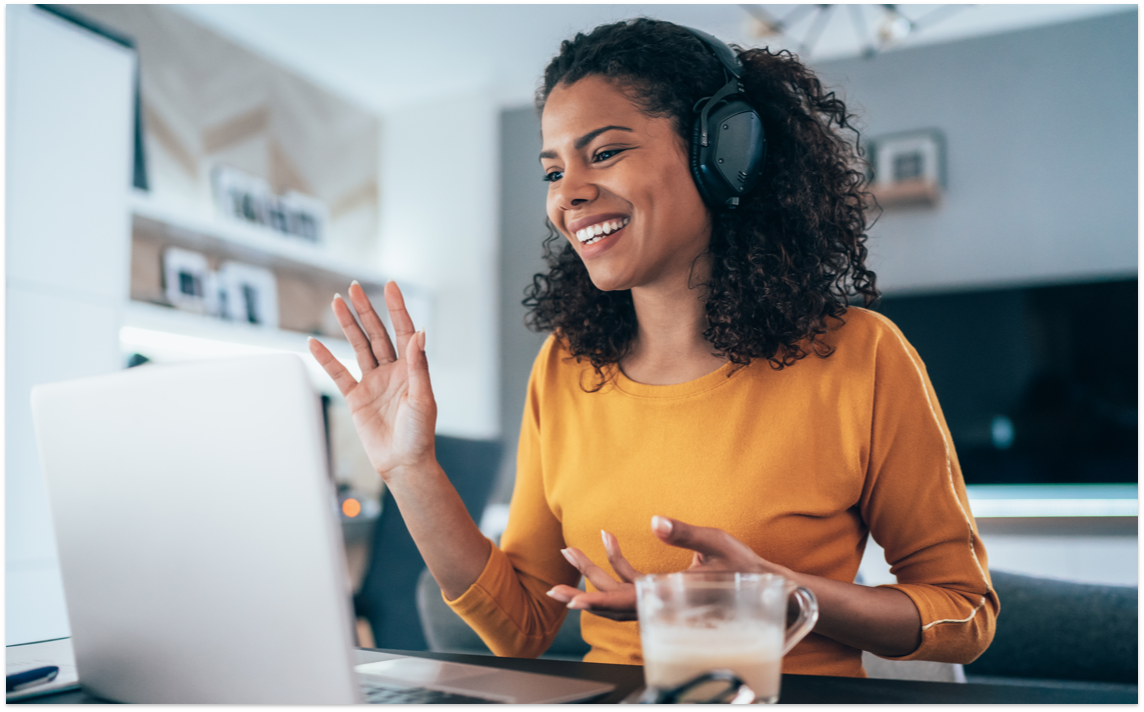 Smiling woman in headphones using a laptop to have a virtual conversation.