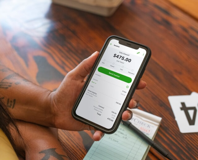 Woman accepting payments through QuickBooks Online on her phone