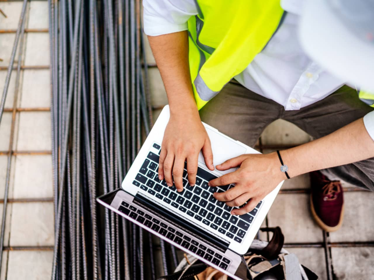 Close up details of engineer working on laptop on construction site.