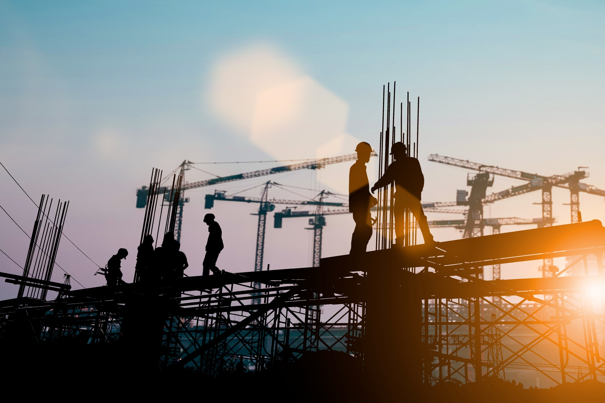 Construction workers building a building at sunset.