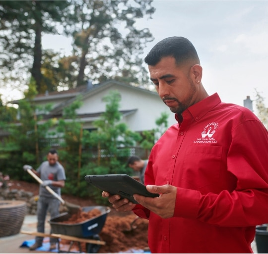 Landscaping business owner checks project status on his device on the job.