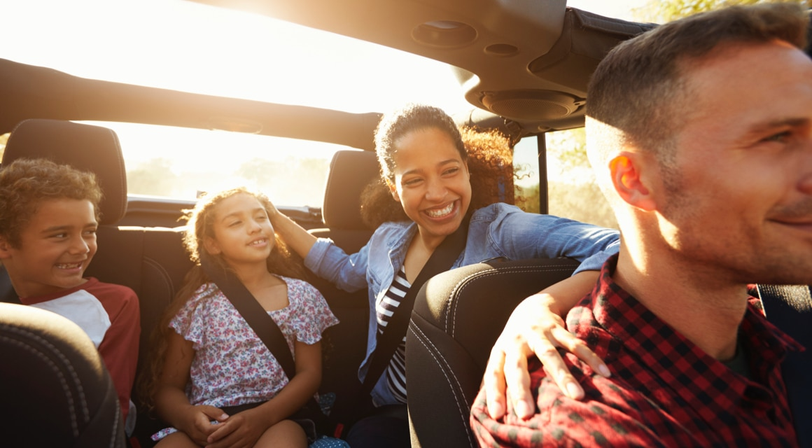 Dad driving with his family in a car.