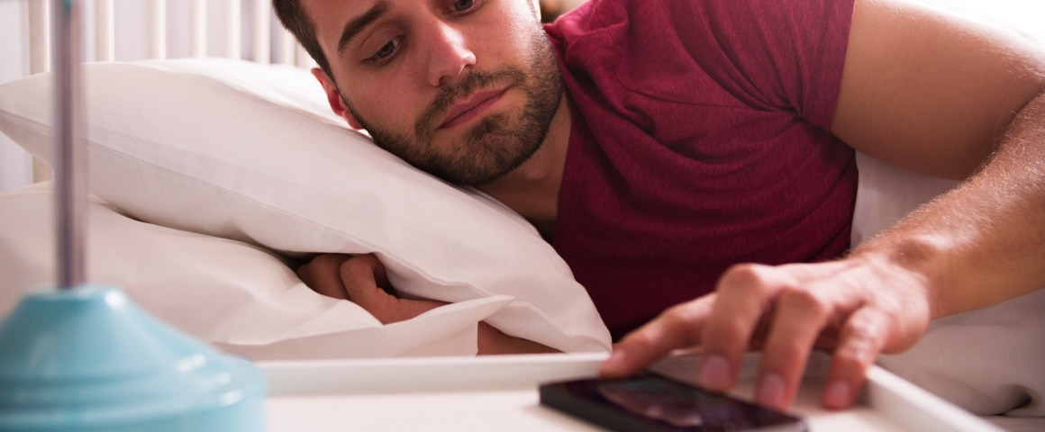 Worker looking at his phone before going to bed.