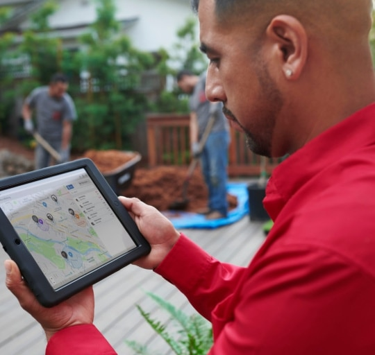 Landscaping services owner using GPS time tracking desktop app on a tablet to track his workers.