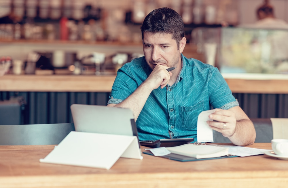 Small business owner doing accounting equations at home on computer