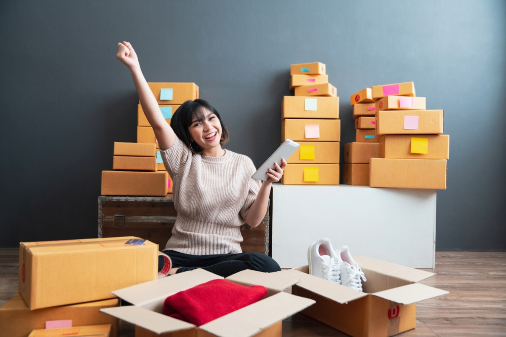 Woman happy as she's packing boxes of clothes and shoes with tablet in hand.