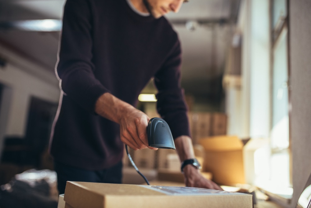 Man using a barcode scanner to scan a barcode on a box.