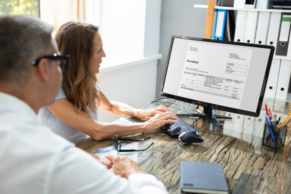 A man and a woman sitting next to each other at a desk looking at an invoice on the monitor while the woman types.