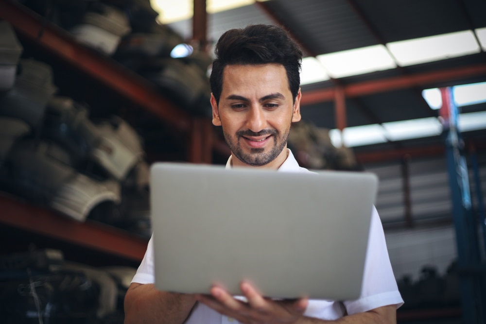 Business owner standing in a warehouse checking his laptop.