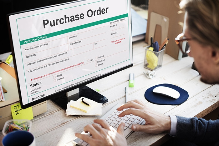 Man sitting at wood desk filling out a purchase order on a computer.