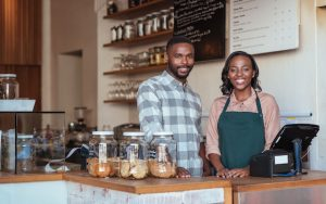 Portrait of two smiling young African entrepreneurs standing welcomingly together behind the counter of their trendy cafe.